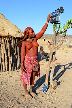 Himba woman turning on her solar powered radio, Etanga, Kaokoland, Namibia. October 2015