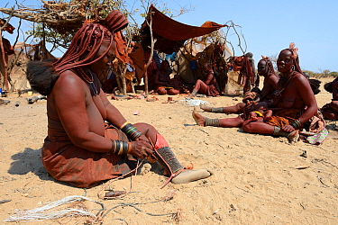 Himba woman adjusting her traditional 'Omohanga' foot ornament, a 21 strand layered anklet, indicating if she is married and has children, Marienfluss Valley. Kaokoland, Namibia October 2015