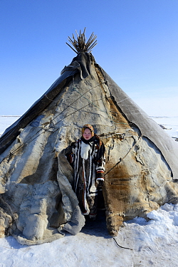 Carolina Serotetto, Nenet teenager at entrance of reindeer fur covered tent, warmly dressed in traditional coat. Yar-Sale district. Yamal, Northwest Siberia, Russia.  April 2016.