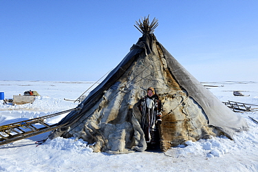Carolina Serotetto, Nenet teenager standing at entrance of her reindeer fur covered tent, warmly dressed in traditional coat. Yar-Sale district. Yamal, Northwest Siberia, Russia. April 2016.