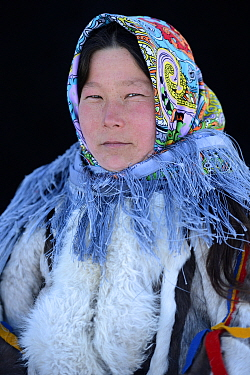 Ekaterina Yaptik, portrait of Nenet herder in winter coat of reindeer fur. The collar is arctic fox fur with black beaver fur and felt ribbons. Yar-Sale district, Yamal, Northwest Siberia, Russia. Apr...