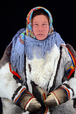 Ekaterina Yaptik, portrait of Nenet herder in winter coat made of reindeer fur. The collar is arctic fox fur with black beaver straps and felt ribbons. Yar-Sale district, Yamal, Northwest Siberia, Rus...
