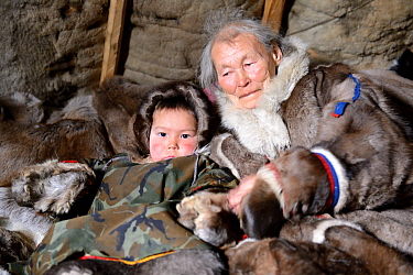 Nenet elder with grandson dressed in winter coats, made from reindeer skin in tent. Yar-Sale district, Yamal, Northwest Siberia, Russia. April 2016.