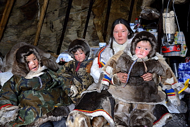 Nenet herder inside tent with daughter and sons, wearing coats made with reindeer skin and fur. Yar-Sale district. Yamal, Northwest Siberia, Russia. April  2016.