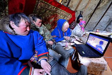 Nenet herders watching laptop inside tent. Yar-Sale district, Yamal, Northwest Siberia, Russia. April 2016.