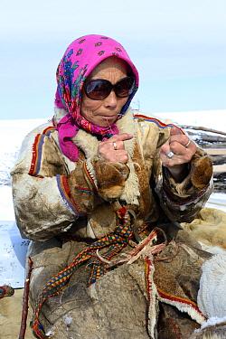 Nenet woman spinning reindeer sinew to sew reindeer skin. Yar-Sale district. Yamal, Northwest Siberia, Russia. April 2016.