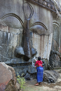 Pilgrim carrying out morning cleaning ritual on a carving of Shiva at 7th-9th century Hindu sacred site. Unakoti, Tripura, India, March 2012.