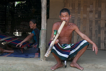 Man of Chakma tribe, smoking a bamboo pipe (daba), with woman weaving on loom in background. Tripura, India, March 2012.
