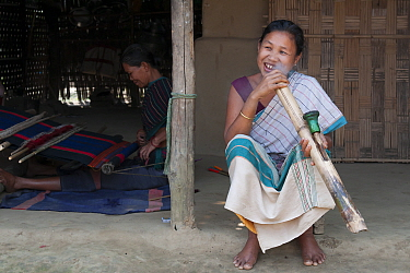 Woman of Chakma tribe, smoking a bamboo pipe (daba), with man weaving on loom in background. Tripura, India, March 2012.