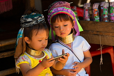 Kayan girls with neck rings looking at smartphone, Thailand. November 2015.