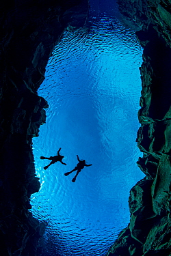 Pair of divers floating in Silfra Canyon, a deep fault filled with fresh water in the rift valley between the Eurasian and American tectonic plates) at Thingvellir National Park, Iceland. May 2011.  I...
