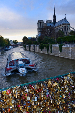 Padlocks on the Pont de l'Archeveche bridge and Notre Dame Cathedral, with boat passing, Paris, France, October 2013.