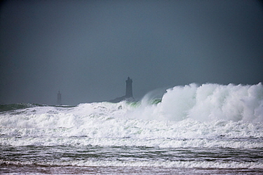 Rough sea during winter storm in Baie des Trepasses / Bay of the Dead, with La Vieille ('The Old Lady') Lighthouse visible in distance. Plogoff, Finistere. Brittany, France, February 2014.