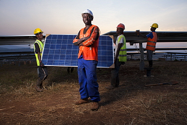 Technicians installing panels in one of East Africa's largest Solar farms, Rwamagana District, Rwanda. July 2014. Model released.