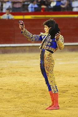 Matador with ear of bull, a 'trofeo' or trophy for a good performance, Plaza de Toros, Valencia, Spain. July 2014.