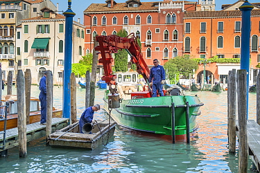 Maintenance barge repairing mooring posts on Grand Canal, Venice, Italy.