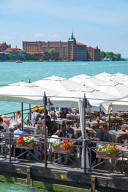 Diners on floating pontoon restaurant with Hilton Molino Stucky Venice on Giudecca Island in distance, Italy, April.