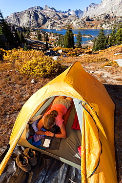 Camper reading inside tent above Island Lake, Wind River Range, Bridger Wilderness, Bridger National Forest, Wyoming, USA. September 2015. Model released.