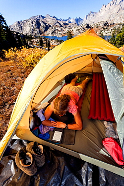Woman Camper reading in tent above Island Lake, Wind River Range, Bridger Wilderness, Bridger National Forest, Wyoming, USA. September 2015. Model released.