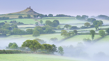 Mist over rolling countryside with distant Brentor Church, Dartmoor, Devon, England, UK. August 2015.