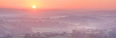 Sunrise over misty countryside, Dartmoor, Devon, England, UK. October 2015.