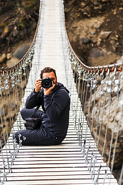 Photographer on footbridge, W Trek. Torres del Paine National Park, Patagonia, Chile. January 2014. Model released.
