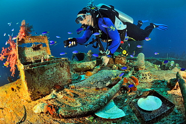 A diver on the wreck of the Shinkoku Maru, a tanker colonized by corals, sponges and other invertebrates, with various remains on the foreground such as bottles, pots and lighting a medical first aid...