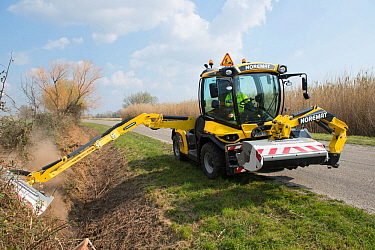Digger clearing ditch at Notre Dame d'Amour, Camargue, France, March.