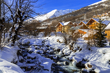 La Valoirette mountain river in winter in front of Valloire ski resort, Savoie in the French Alps. Maurienne Valley, France