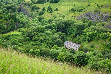 Railway cottages, Chee Dale, Peak District National Park, Derbyshire, UK. Quarried limestone rockfaces can be seen along the ridge above.
