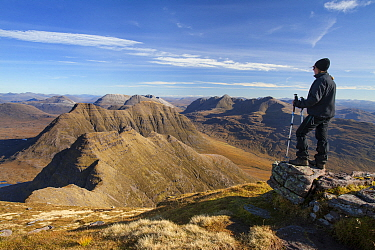 Hiker looking out from Sgurr Mor towards Torridonian mountains, Wester Ross, Scotland, UK, October 2015.