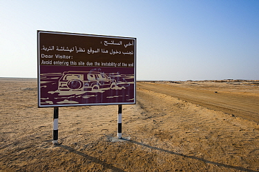 Sign warning about the danger of soft, mixed mud-salt-flats, locally known as 'sabkhas', Bar Al Hikman , Sultanate of Oman, February.