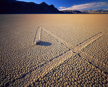 Boulder with zig-zag trails across a dry lake bed, sunset, Ubehebe Peak in distance, The Racetrack Playa, Death Valley National Park, California