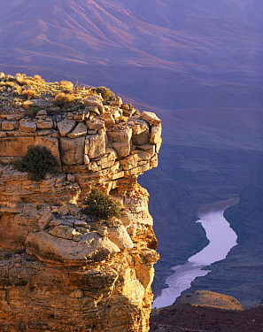 Sunrise on stratified rim rock tower at Grandview Point with meandering Colorado River riffle below, Grand Canyon National Park, Arizona, USA.
