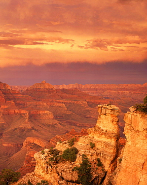 Sunset at Yaki Point on the South Rim with stratified rim rocks and minute storm clouds inside the canyon below, Grand Canyon National Park, Arizona, USA.