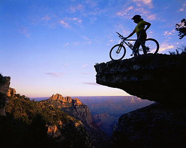 Mountain Biker stood on a ridge at sunrise overlooking the Grand Canyon, Grand Canyon NP, Arizona, USA