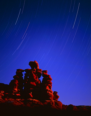 Hoodoo formations of heavily banded sandstone at night with star trails, Navajo Reservation, Arizona, USA