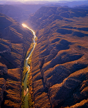 Aerial view of Rio Grande passing through the Boquillas Canyon with the Chisos Mountains and Big Bend National Park in the background, Texas, USA on right of river, Mexico on left of river.