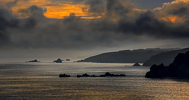 Silhouette of cliffs at the Pointe de Penharn at sunrise with storm clouds, Cl�den-Cap-Sizun, Finist�re, Brittany, France, September 2015.