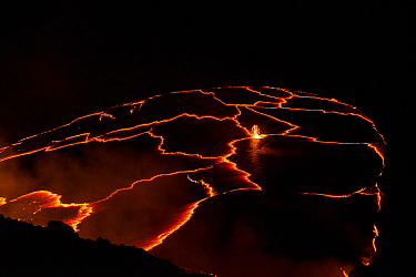 Molten lava boils at night in a lava lake in a pit below the crater floor of Halemaumau Crater, Kilauea Volcano, Hawaii. Red-orange jagged lines are junctures between plates of hard cooled lava floati...
