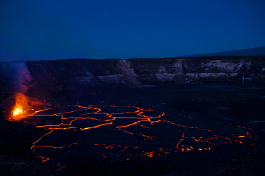Hot lava fountains at a subduction zone at the edge of a lava lake, covered by plates of partially solidified cooled lava floating on its surface, in a pit within Halemaumau Crater, Kilauea Volcano, H...