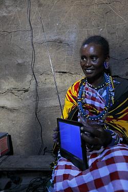 Masai woman with portable television, powered by solar energy,  Masai Mara, Kenya. March 2013.
