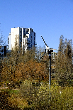 Wind turbine in urban setting with flats behind, Mile End Park London Borough of Tower Hamlets, England, UK, March 2014.