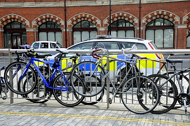 Bikes attached to railings showing the need for more bicycle racks in the vacinity of the station, Kings Cross, London, England, UK, August 2014.