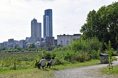 Couple sitting on camping chairs on urban nature reserve with tower blocks in distance, Woodberry Wetlands, Stoke Newington, Hackney, England, Britain, UK, August 2016.