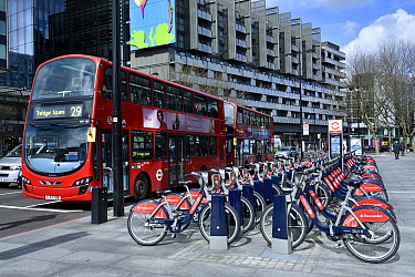 Santander Cycles or Boris Bikes, bicycle hire scheme docking station with number 29 bus, corner of Hampstead Road and Euston Road, Camden, England, UK, March 2016.