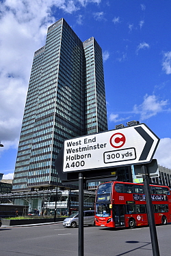 Traffic direction sign with congestion charge symbol, bus and Euston Tower in background, Euston Road, Central London, UK, March 2016.