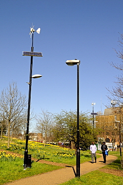 Wind and solar powered lamppost or lamp post alongside conventional lamppost with people passing, Mile End Park, London Borough of Tower Hamlets, England, UK, March 2014.