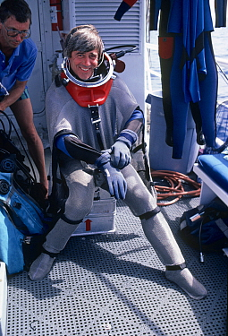 Mike DeGruy preparing to dive in shark suit. California, USA