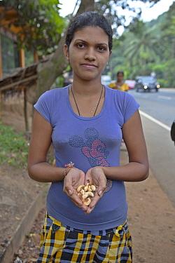 Young girl selling cashews at roadside, Gampaha, Sri Lanka, December 2012.